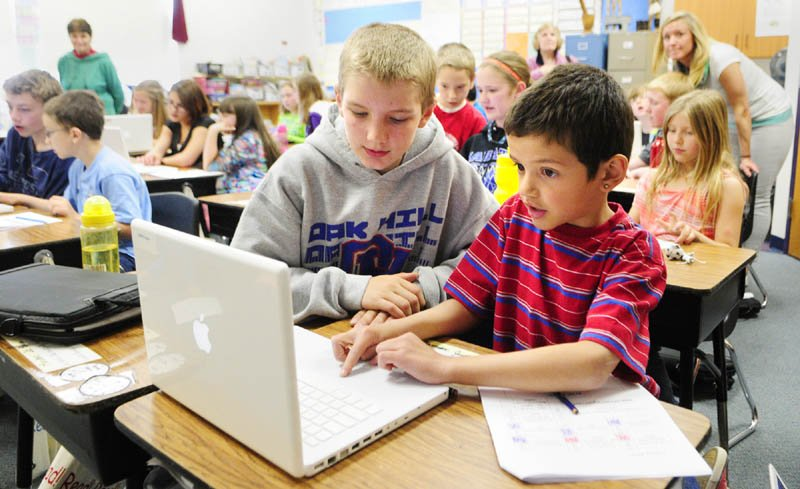 Oak Hill Middle School seventh-grader Eric O'Connor, left, works with a Carrie Ricker School third-grader on an Apple MacBook last month in Litchfield. Maine teachers are overwhelmingly choosing Apple products for their students, the state says.