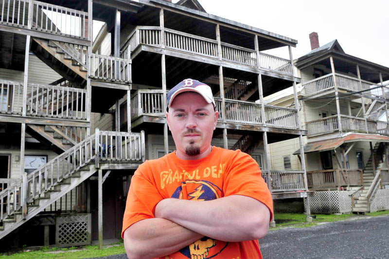 Bobbi Frappier stands outside the Waterville apartment building known as the