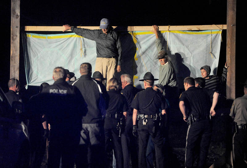 Authorities approach members from 350 Maine, who blocked the railroad crossing at Lawrence Avenue in Fairfield Thursday night, to protest the transport of fracked oil.