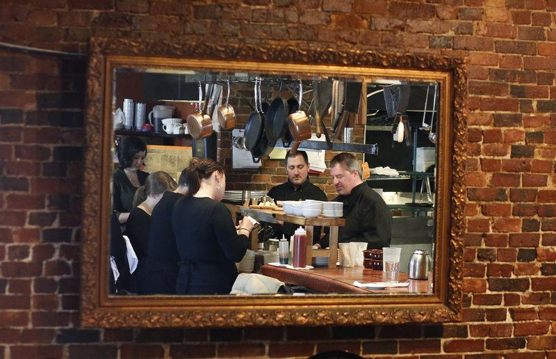 A mirror at The Grill Room & Bar in Portland reflects chef and restaurateur Harding Lee Smith as he meets with his staff recently. A fellow chef in Portland who used to work for Smith describes him as extremely demanding but fiercely loyal to employees who work hard and show loyalty to him.