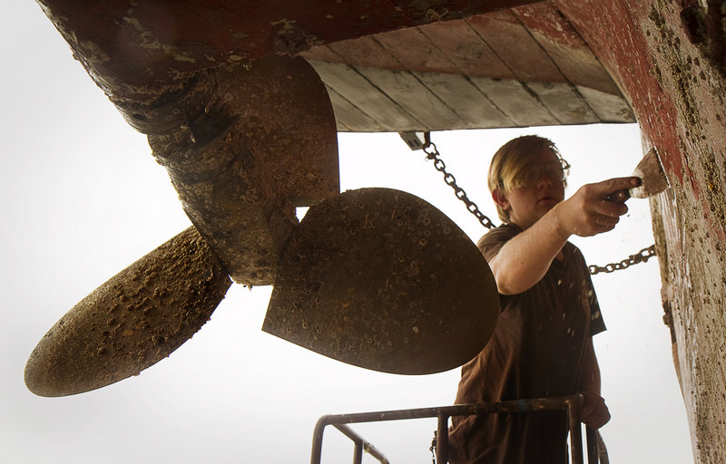Crew member Andrew Duzs, of the former slave ship Amistad, scrapes barnacles from the hull in dry dock at Gowen Marine in Portland on Thursday June 13, 2013.