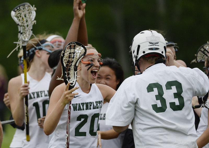 Cat Johnson, 20, of Waynflete rushes to celebrate with goalie Katherine Torrey after the 16-9 victory against Cape Elizabeth put the Flyers into the Class B girls' lacrosse state championship game Saturday against Yarmouth.