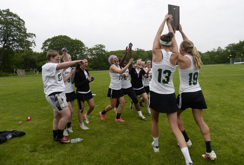 Sadie Cole, 13, and Martha Veroneau of Waynflete carry the regional championship plaque to their teammates after the victory against Cape Elizabeth. Waynflete will meet Yarmouth in the state final Saturday.