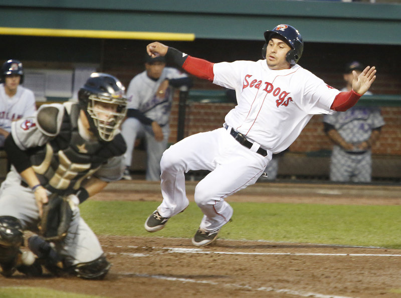 Ryan Dent of the Sea Dogs slides into the plate Friday night to score on a single by Heiker Meneses in the fourth inning of a 6-2 loss to the Akron Aeros at Hadlock Field. The catcher is Jake Lowery.