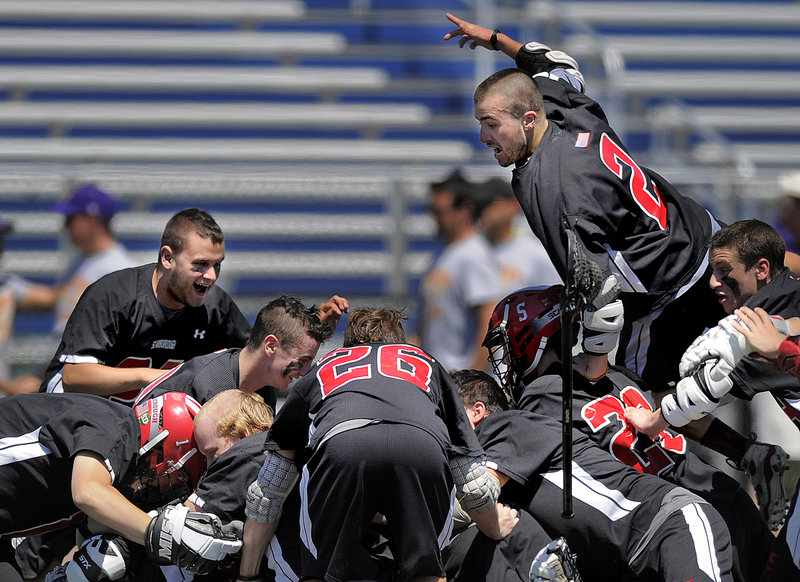 Jurien Garrison, top, jumps onto the pile after Scarborough became the first lacrosse team to win four consecutive state championships since the Maine Principals' Association started sponsoring the sport in 1998.