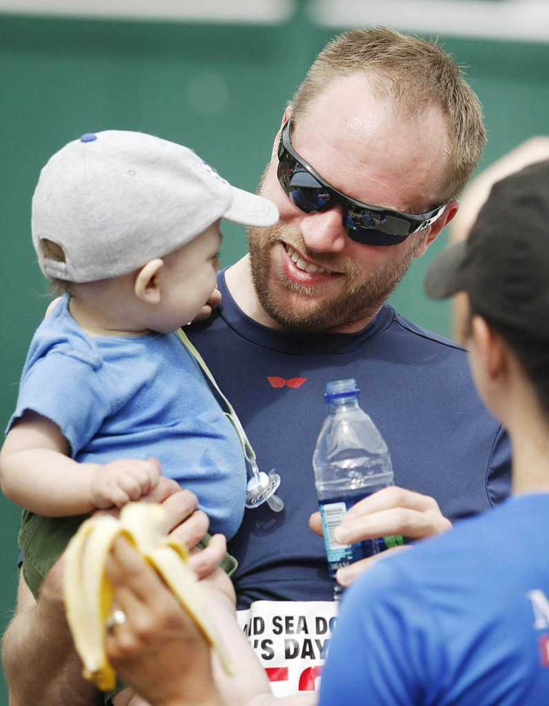 Jason Worswick of South Portland holds his young son, Griffin, after running the Portland Sea Dogs Father's Day 5K Sunday.