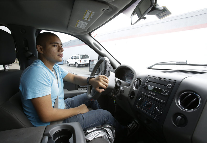 Francis Tume drives his truck in Miami, one year after President Obama announced an executive order allowing young people living in the United States illegally to stay and work.