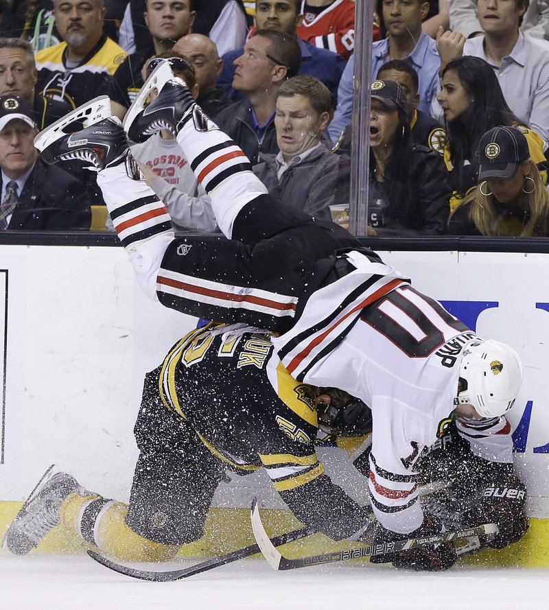 Bruins defenseman Johnny Boychuk upends Chicago's Patrick Sharp along the boards in the third period of Game 4.