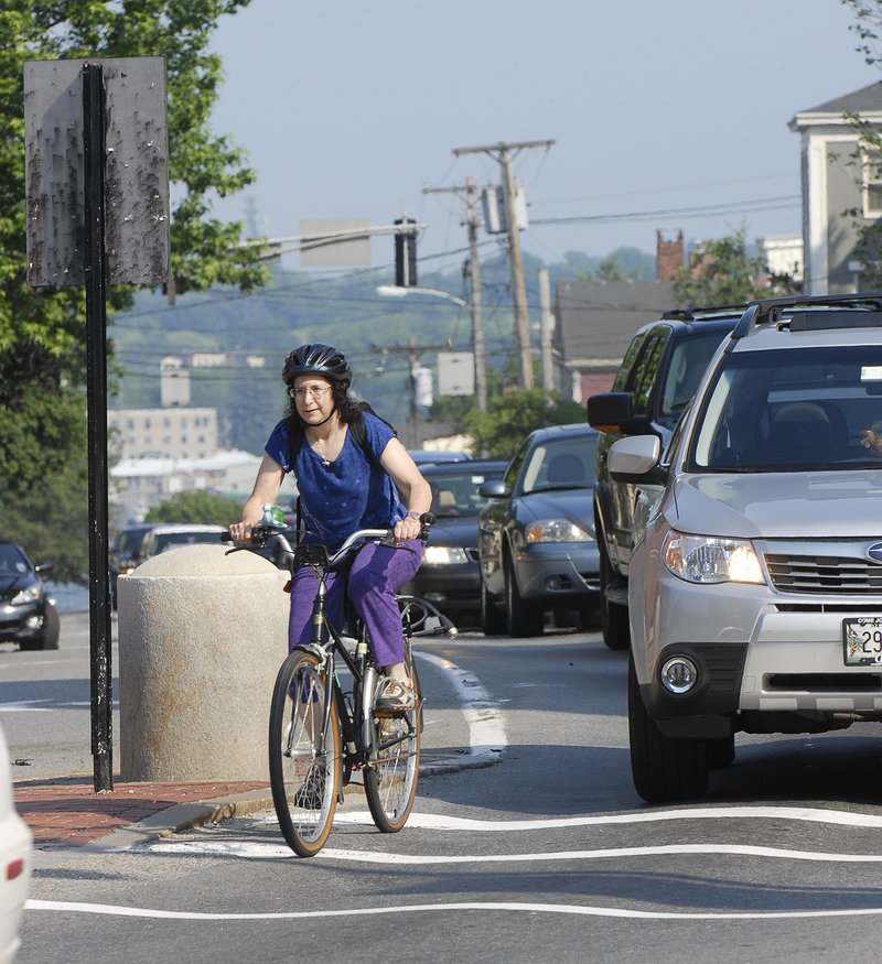 """A bicycle commuter navigates traffic in Portland in 2008. A reader says, """"I am a driver and a cyclist, and when in my car I see much more bad, rude and dangerous driving from other motorists than I ever do from cyclists."""""""