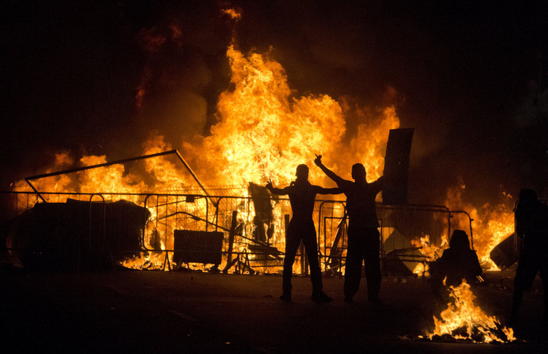 Protesters taunt riot police as they stand in front of a burning barricade during an anti-government protest in Rio de Janeiro on Thursday.