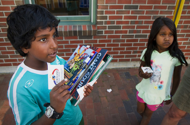 Toby Picher, 9, with an arm-full of books, and sister Cora, 6, show off their first library cards obtained from the Portland Public Library's mobile unit outside The Root Cellar on Washington Avenue on Friday, June 21, 2013. Students and parents can access books from the mobile unit, which will make regular visits around Portland throughout the summer vacation.