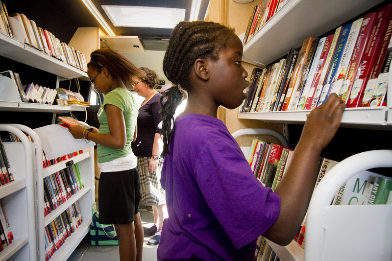 Lina Wakati, 9 of Portland, chooses books from the Portland Public Library's mobile unit in front of The Root Cellar on Washington Avenue in Portland. The mobile unit will make regular visits around Portland throughout the summer, supplying books to kids over the summer vacation.