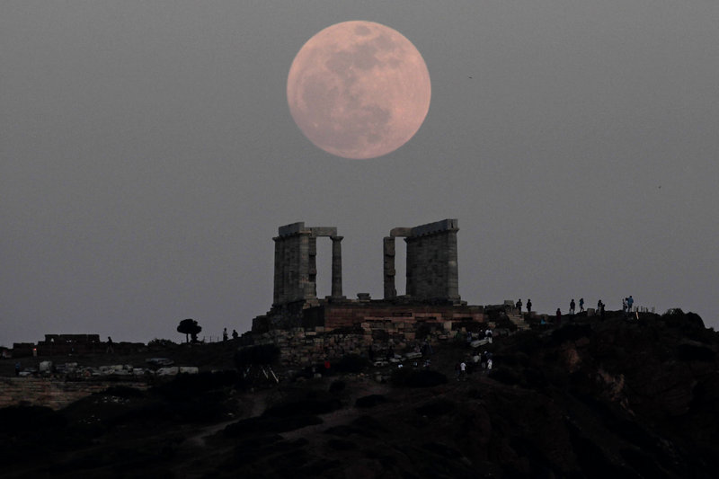 "Gracing the sky above the Temple of Poseidon in Cape Sounion, Greece, is a classic ""supermoon."""