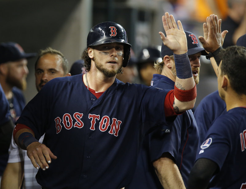 Jarrod Saltalamacchia of the Boston Red Sox gets the welcome-home from teammates in the dugout after scoring on Shane Victorino's grounder in the eighth inning of a 10-6 victory against Detroit Friday night.