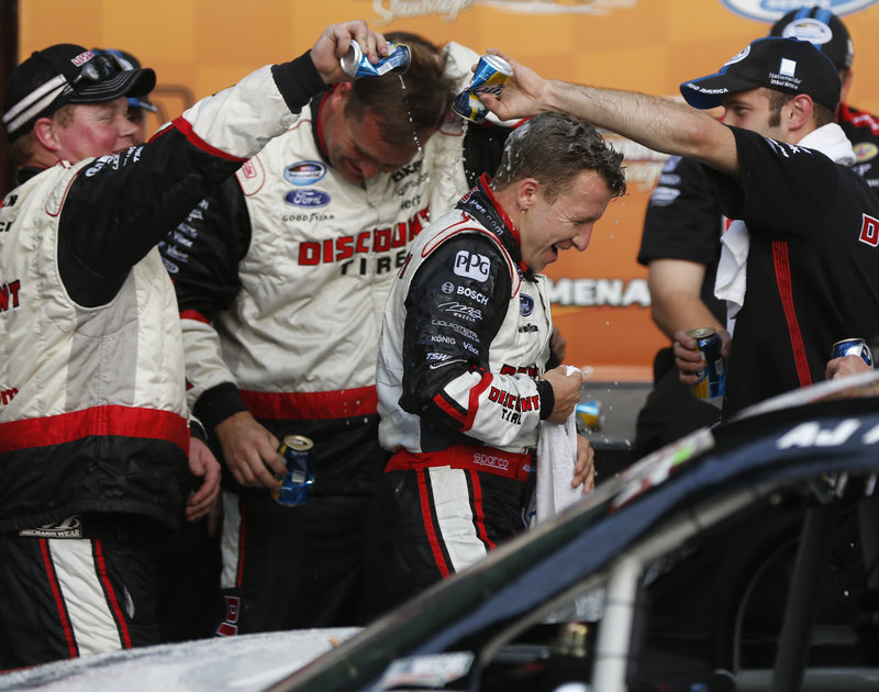 AJ Allmendinger celebrates with crew members after winning the Nationwide Series race Saturday on the road course at Elkhart Lake, Wis.