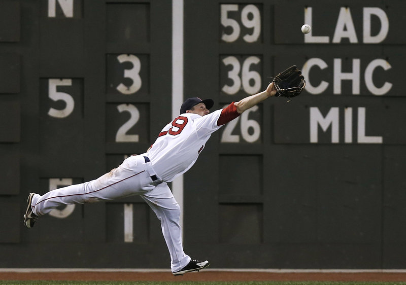 Left fielder Daniel Nava of the Boston Red Sox stretches Tuesday night in a bid to haul in a ball hit by Carlos Gonzalez of the Colorado Rockies in the seventh inning at Fenway Park. The ball dropped in for a single.