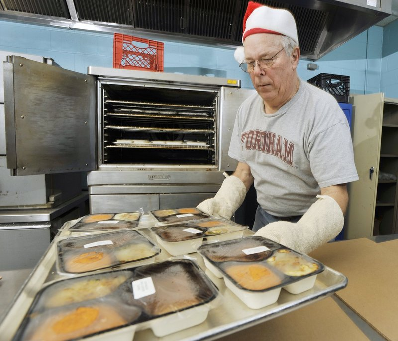 Volunteer Tom O'Connor pulls prepared holiday meals from the oven, where they were heated before being delivered to Meals on Wheels recipients in southern Maine in 2011. A minister who helped bring the program to Maine says he fears for its future.