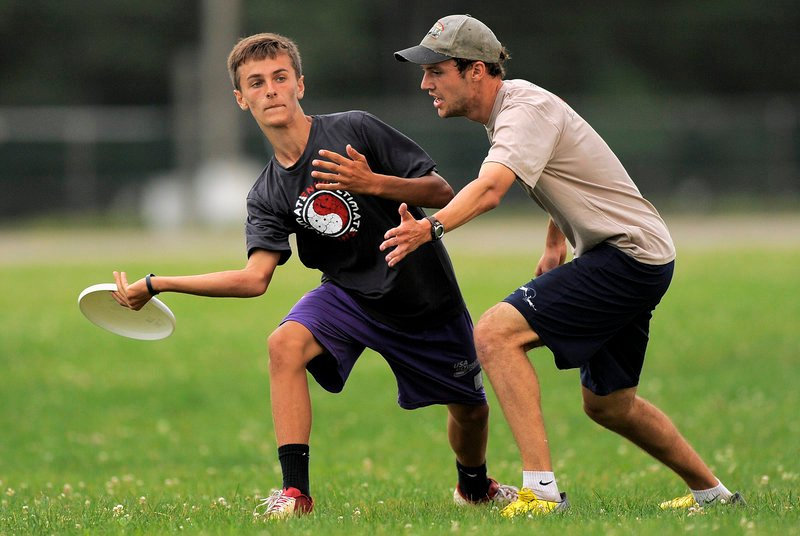 Nick Plummer, a member of Rising Tide, looks to throw around Nate Buck of the New Gloucester Village Store during their game.