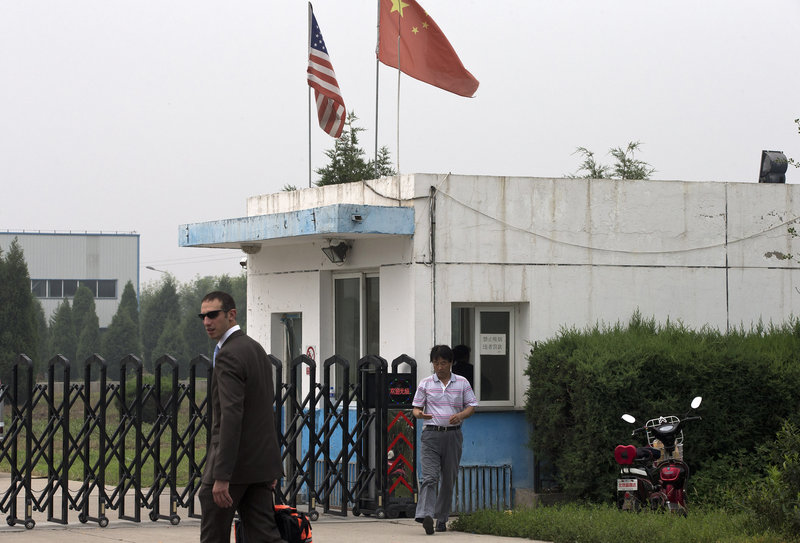 A U.S. Embassy employee and a Chinese official walk outside the closed gate at a plant where an American was being held.