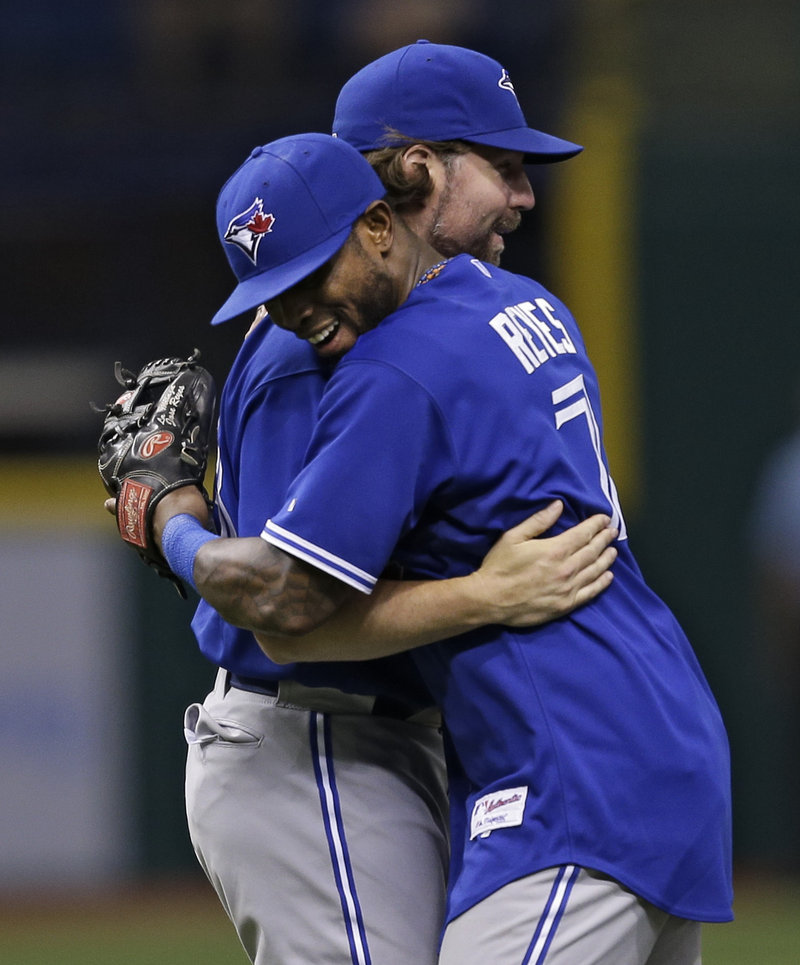 Toronto shortstop Jose Reyes (7) hugs starting pitcher R.A. Dickey after the Blue Jays defeated the host Rays, 3-0.
