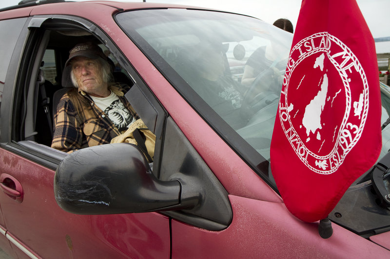 Michael Kilgore sits in the passenger seat of a car displaying the Long Island town flag. The car is owned by island resident Lorinda Vallas.