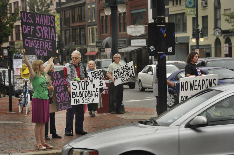 Displaying hand-made signs, demonstrators gather on a corner of Portland's Congress Square, Friday, to protest U.S. involvement in the war in Syria.