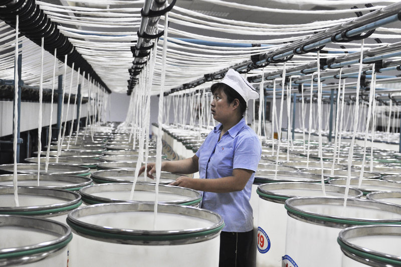 A woman works in a textile factory Wednesday in Zouping, Shandong province, eastern China. Factory equipment exports from the United States could be hurt if credit-starved manufacturers put off purchases.