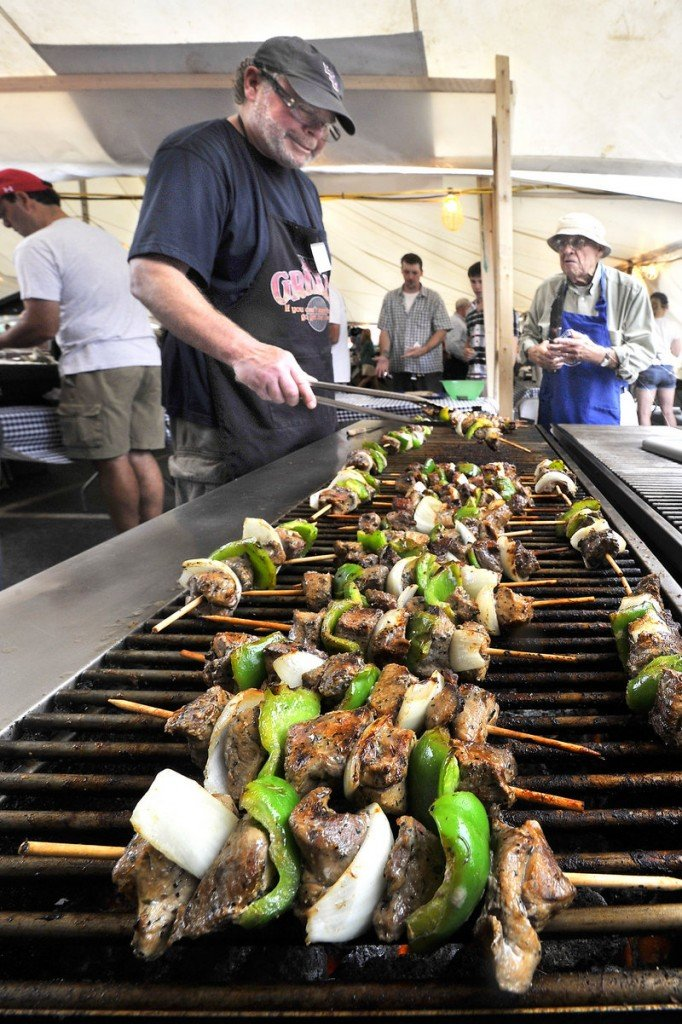 Byron Neal grills lamb souvlaki with help from Christopher Makrides, right, Saturday at the Greek Food Festival held at the Holy Trinity Greek Orthodox Church in Portland.
