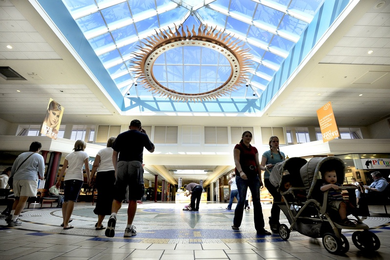 Shoppers crisscross the center atrium of The Maine Mall in South Portland. The mall has abandoned an appeal of its tax assessment.