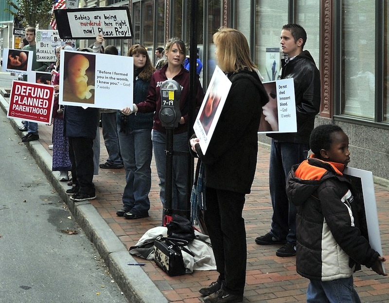 In this October 2012 file photo, anti-abortion demonstrators protest with graphic signs outside the Planned Parenthood of New England agency on Congress Street in Portland, Maine. At a meeting of a City Council subcommittee Tuesday, the Portland Police Department will report on the weekly anti-abortion protests outside Planned Parenthood's clinic on 443 Congress St.