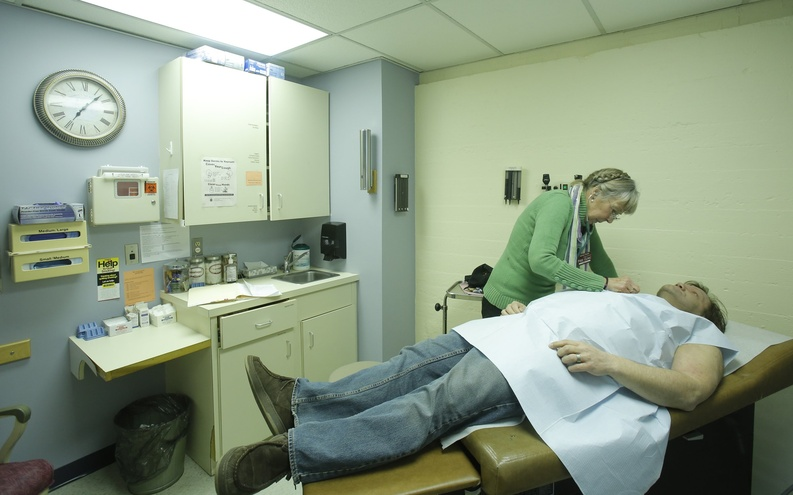 A nurse practitioner at the India Street Public Health Clinic in Portland examines a patient.