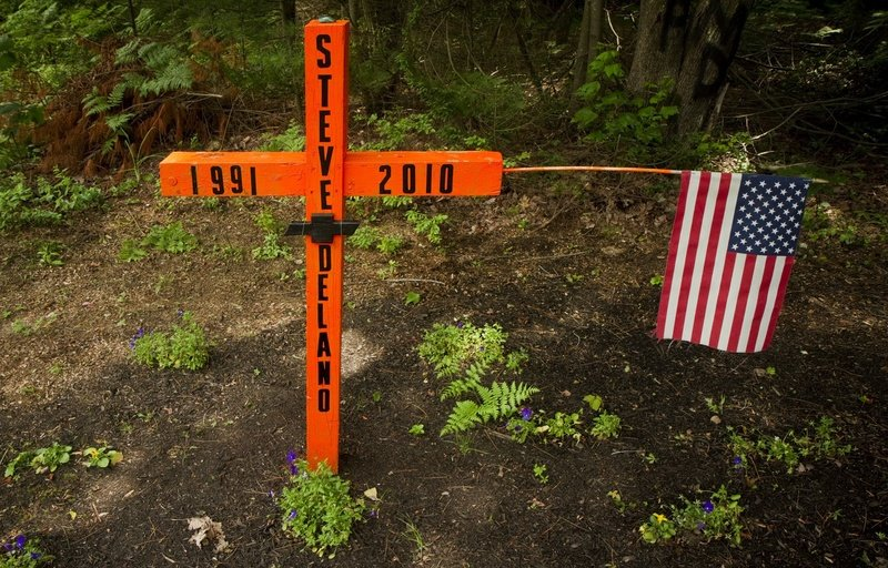 A roadside memorial occupies the location of a fatal accident on Payne Road in Scarborough. The Town Council has put off consideration of an ordinance to regulate such displays.