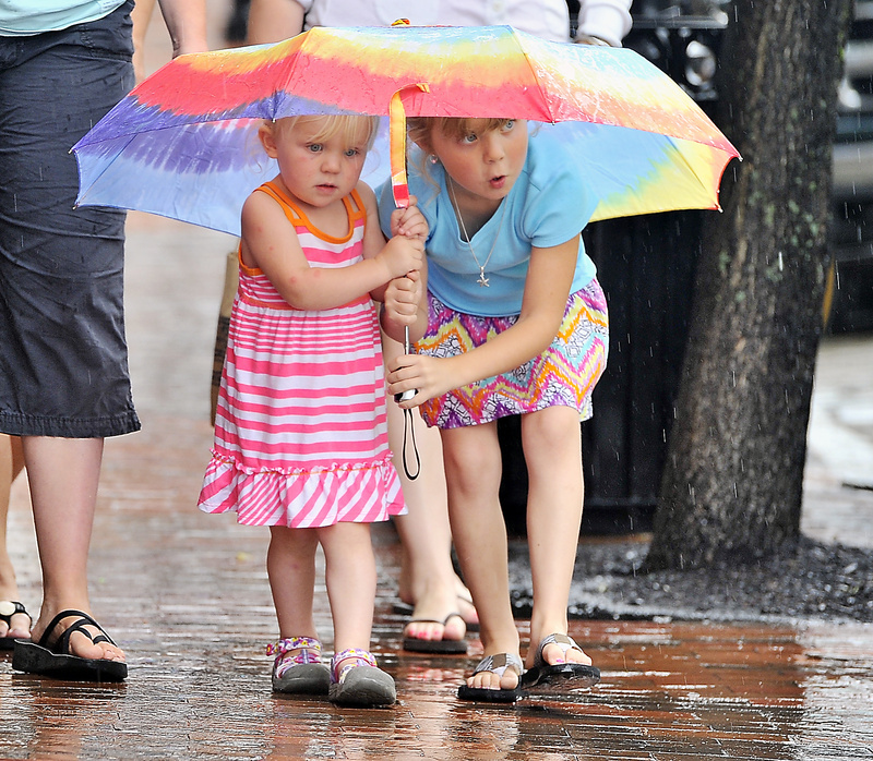 Quinn Sawyer, 4, left, and her sister, Summer, 6, take protection from the rain with their colorful umbrella as they walk on Moulton Street in the Old Port with their mother, Jessi Sawyer of Weld, and other family members Monday.