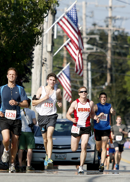Competitors run up Main Street near the finish line during the L.L.Bean Fourth of July 10K Road Race in Freeport.