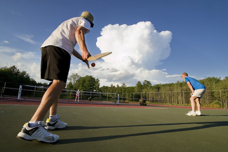 A pickleball player gets ready to serve while playing at Sunset Ridge Golf Course in Westbrook on Friday, July 5, 2013. Pickleball is a game similar to tennis, played with oversized ping pong paddles and a plastic ball like a whiffleball on a small tennis court with a 34-inch net.