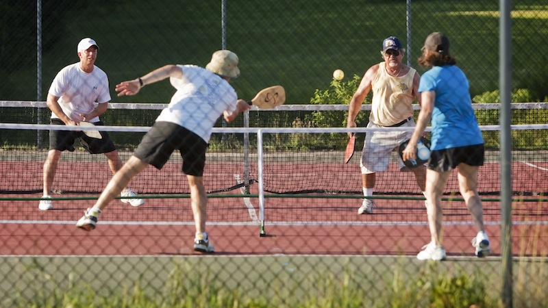 Teams of doubles compete during a pickleball match at Sunset Ridge Golf Course in Westbrook on Friday, July 5, 2013. Pickleball is a game similar to tennis, played with oversized ping pong paddles and a plastic ball like a whiffleball on a small tennis court with a 34-inch net.