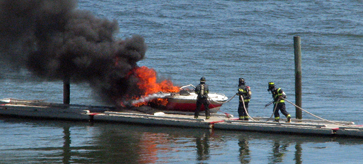 Firefighters extinguish a boat fire at East End Beach in Portland on Friday.