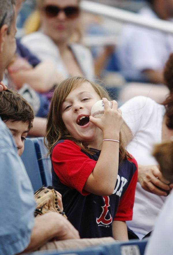 Grey Roessler, 7, of Florence, Mass., shows her dad, Jo, far left, how a baseball that was tossed to her by a Portland Sea Dogs player bonked her on the cheek during Monday's game vs. the New Britain Rock Cats at Hadlock Field in Portland, July 8, 2013. In addition to her dad, Grey was with her mom, Nora, and her twin brother, Gerrit, 7.