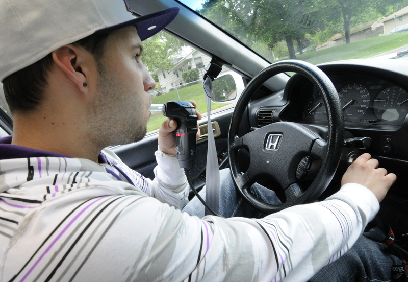 Zachary Glaros, who has three drunken-driving convictions on his record, demonstrates the interlock ignition system that requires him to blow into a tube to prove he is sober before starting his car, at his Bloomington, Minn., home. A new Maine law allows people convicted of drunken-driving to shorten their license suspensions if they use such a device.