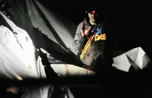 In this Massachusetts State Police photo, 19-year-old Boston Marathon bombing suspect Dzhokhar Tsarnaev, bloody and disheveled with the red dot of a sniper's rifle laser sight on his forehead, raises his hand from inside a boat at the time of his capture by law enforcement authorities in Watertown, Mass.