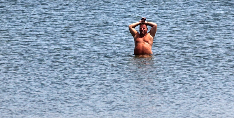 A man cools off on the shore of Castle Island in the South Boston neighborhood Wednesday. Temperatures in the Boston area reached the 90s, extending a heat wave.