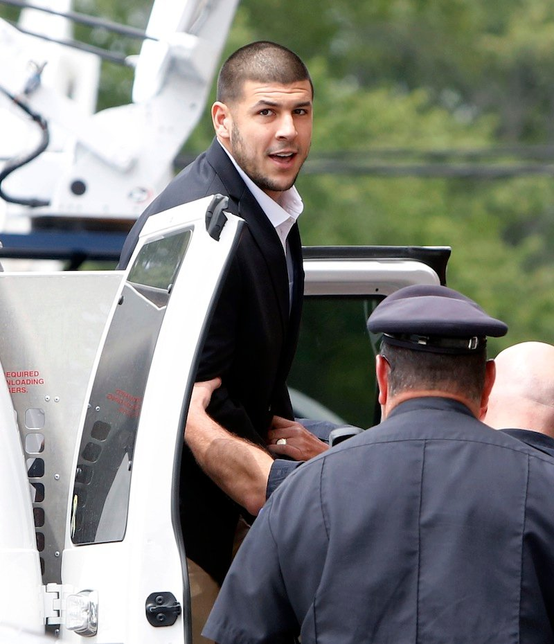 Former New England Patriots NFL football tight end Aaron Hernandez is led out of a van as he arrives for his probable cause hearing at Attleboro District Court on Wednesday in Attleboro, Mass. Newly released surveillance photos show former New England Patriot Aaron Hernandez holding what authorities say appears to be a gun, shortly after his friend was shot to death.