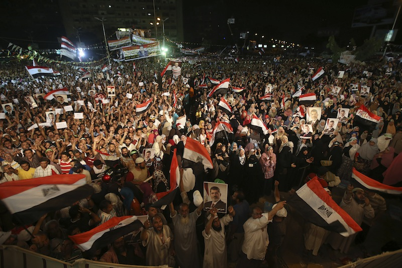 Supporters of the ousted Egypt's President Mohammed Morsi, hold his portraits and wave Egyptian flags as they shout slogans during a demonstration after the Iftar prayer, evening meal when Muslims break their fast during the Islamic month of Ramadan, in Nasr City, Cairo, Egypt, Wednesday July 10, 2013. Egypt's military-backed government tightened a crackdown on the Muslim Brotherhood on Wednesday, ordering the arrest of its revered leader in a bid to choke off the group's campaign to reinstate President Mohammed Morsi one week after an army-led coup. (AP Photo/Hussein Malla)