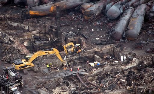 Workers comb through the debris Tuesday in Lac-Megantic, Quebec.