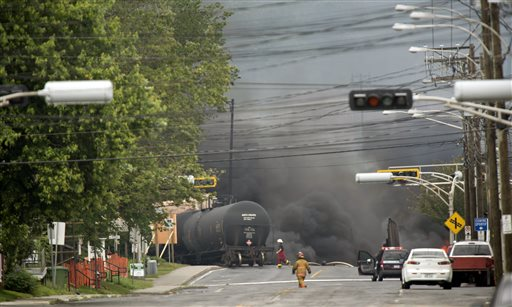 In this July 6 file photo, smoke rises from derailed railway cars that were carrying crude oil in downtown Lac-Megantic, Quebec, Canada. The Maine company that owns the train that derailed and exploded in the center of Lac-Megantic has lost much of its freight business and is struggling financially because of the crash.
