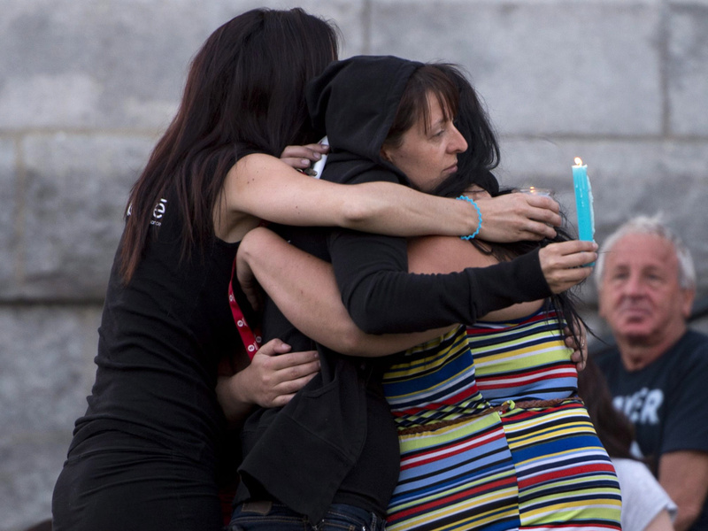 People comfort each other in front of the St-Agnes church during a vigil for the victims of the train crash in Lac-Megantic, Quebec, on July 12. Police raided the railway's Canadian office in a search for evidence Thursday, July 25, 2013.