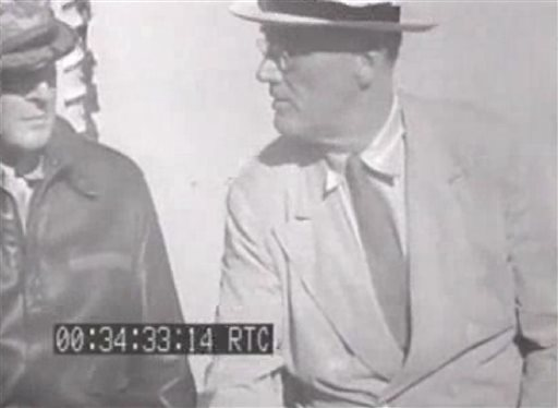 This image from an eight-second film clip provided by the National Archives shows President Franklin Delano Roosevelt, right, aboard the U.S.S. Baltimore in Pearl Harbor in July 1944, depicting a secret not revealed to the public until after his death. Person at left is unidentified.