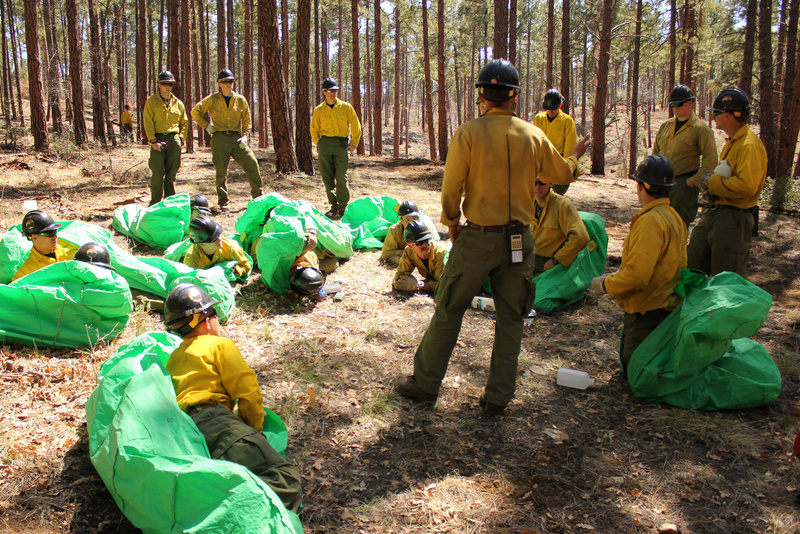 Phillip Maldonado, a squad leader with the Granite Mountain Hotshots, trains crew members on setting up emergency fire shelters last year. On Sunday, June 30, 2013, 19 members of the Prescott, Ariz.-based crew were killed in a wildfire. Arizona Wildfires