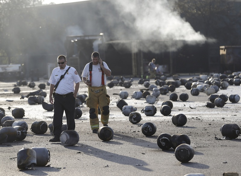 Firefighters walk through an area of exploded propane cylinders in the aftermath of an explosion and fire at a propane gas company, Tuesday, July 30, 2013, in Tavares, Fla. Eight people were injured, with at least three in critical condition. John Herrell of the Lake County Sheriff's Office said early Tuesday there were no fatalities despite massive blasts that ripped through the Blue Rhino propane plant late Monday night. (AP Photo/John Raoux)