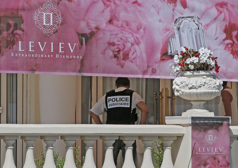 A police officer stands in front of the Carlton Intercontinental Hotel in Cannes, southern France, where $53 million worth of jewels was stolen Sunday.